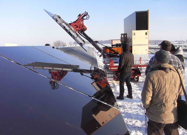 A robotic arm places a large PV panel onto a frame during the construction of a power plant in Leipzig, germany. The panel is around 6 square meters in size and weighs 120 kilograms. credit: Gehrlicher Solar AG