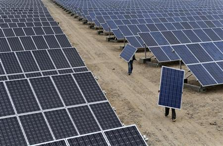 Employees carry solar panels at a solar power plant in Aksu