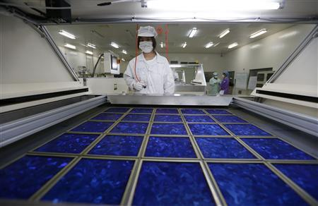 An employee dries newly made solar panels at a factory of a photovoltaic company in Jiaxing