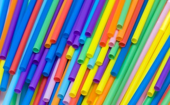 Brightly colored straws thrown around on a table. Some of them are showing the lower side of the tube, with only a few of the flexible heads visible. The colors range from blue to red tones.