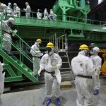 Members of the media and TEPCO employees walk down the steps of a fuel handling machine on the spent fuel pool inside the No.4 reactor building in Fukushima